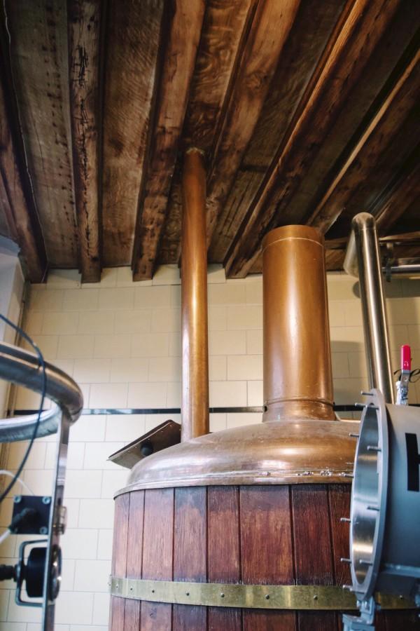 De lange buis boven de ton loopt door naar de zolder waarvanuit de mout (ontkiemde graankorrels) in het vat wordt gegooid.